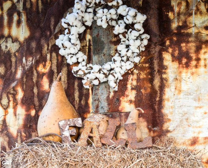 Simple Fall Decorating with hay bales, old tobacco baskets, birdhouse gourds, cotton wreath, and rusty metal letters
