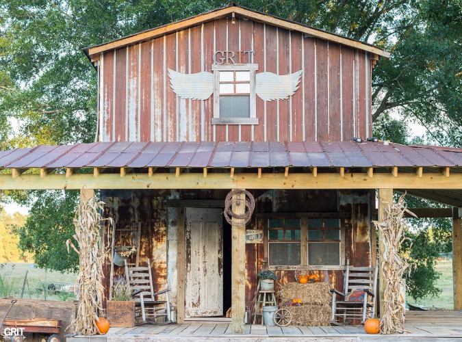 Decorating the barn for Fall using tradition orange pumpkins, hay bales, corn stalks, and rusty antiques.