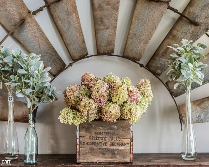 Simple Spring Entryway. Farmhouse style entry with an old windmill & milk crate filled with dried hydrangeas.