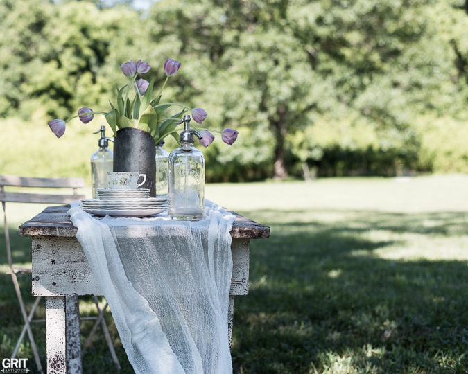 Vintage Summer Table Setting. Old Farm table, voile, vintage dishes, seltzer bottles and old scoop for the flowers.